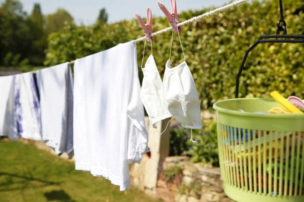 drying white clothing. washing, drying, cleaning of reusable cotton medical surgical mask for protection of coronavirus infection COVID-19. dried on clothesline in open air and sunlight for reuseable stock photo