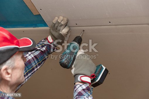 466705128 istock photo Drywall construction, attic renovation. Man fixing drywall suspended ceiling to metal frame using electrical screwdriver 1130317375