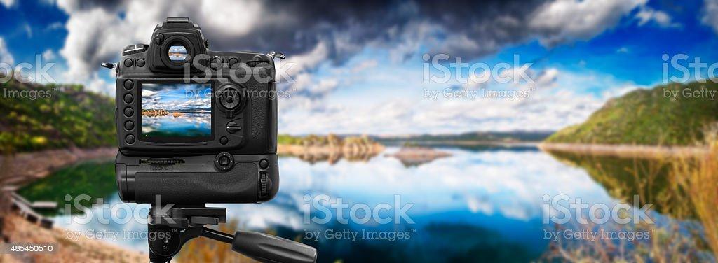 Câmera Dslr fotografar em um lago tranquilo - foto de acervo