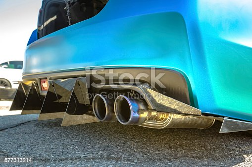 Dual exhaust pipes on a custom car with rear spikes and teal paint. Custom cars in Southern California summer 2017