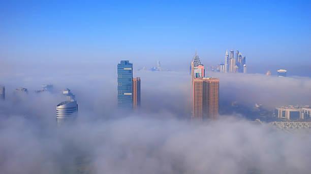 dubai stadt und ist durch frühen morgen nebel - größte städte der welt stock-fotos und bilder