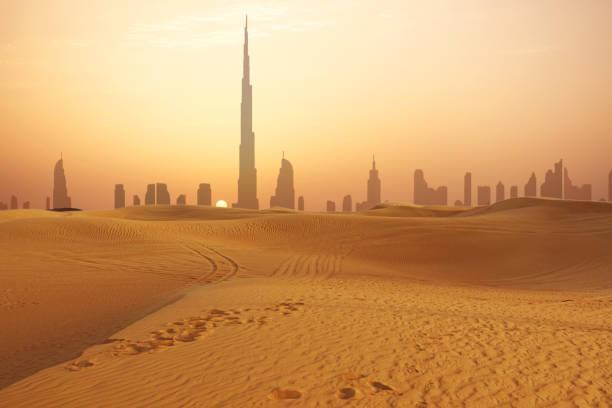 dubai stadt skyline bei sonnenuntergang gesehen aus der wüste - dubai stock-fotos und bilder