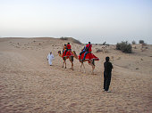 In May 2011, tourists were taking camel rides in Dubaï Desert, United Arab Emirates