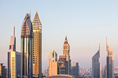 The skyline of Dubai DIFC district during a colorful sunset as viewed from a rooftop. Dubai, UAE.