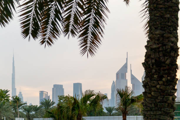 UAE, DUBAI, CIRCA 2021: Dubai Financial center district. View of The Jumeirah Emirates Towers in DIFC and Burj Khalifa. Day view with hazy sky stock photo