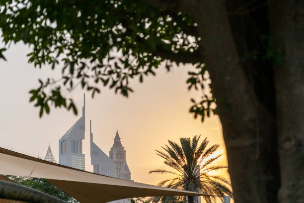 UAE, DUBAI, CIRCA 2021: Dubai Financial center district. View of The Jumeirah Emirates Towers in DIFC and Burj Khalifa. Sunset view with cloudy sky stock photo