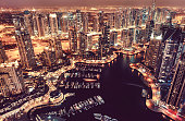 A night view over Dubai Marina at night with lots of tall buildings and boats.