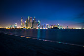 Night shot of Dubai marina, shot from palm Jumeirah. Buildings and sky are illuminated with city lights of different colors. Some boats are seen in front in the sea. A lot of copy space to put your text in.
