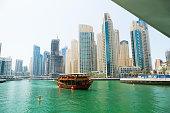 Dubai, UAE- March 28, 2015: Dhow on Dubai Marina; s background are modern skyscrapers with offices, apartments and hotels.