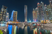Cayan Tower in dubai marina surrounded with beautiful marina towers at night