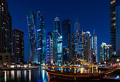 Luxurious Dubai marina skyscrapers and yachts at blue hour