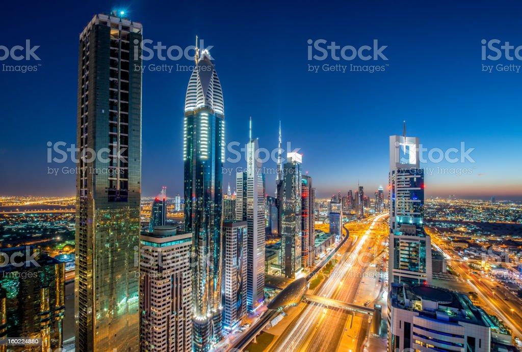 Dubai Megacity Modern Urban Skyscrapers illuminated in the Financial Downtown District of Dubai. Landmarks like Dubai Metro, the Burj Khalifa Tower and Burj Al Arab Hotel are visible on the horizon of this 14mm Ultra Wide Angle Architecture Night Shot. Long Time Exposure, Motion Blured Car Lights. Dubai, United Arab Emirates. Architecture Stock Photo