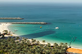 Dubai, United Arab Emirates - January 7, 2013: A panoramic view of Jumeirah Beach with palms, boats and tourists on the beach