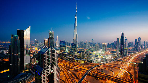 Dubai sky line with traffic junction and Burj Khalifa Dusk view of awesome Dubai's sky line, Aerial view of the city at blue hour. burj khalifa stock pictures, royalty-free photos & images