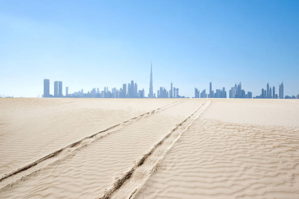 Dubai Skyline and Car Tyre Track in Desert, United Arab Emirates Dubai skyline and car tyre track in desert at clear sky, United Arab Emirates. tire track stock pictures, royalty-free photos & images