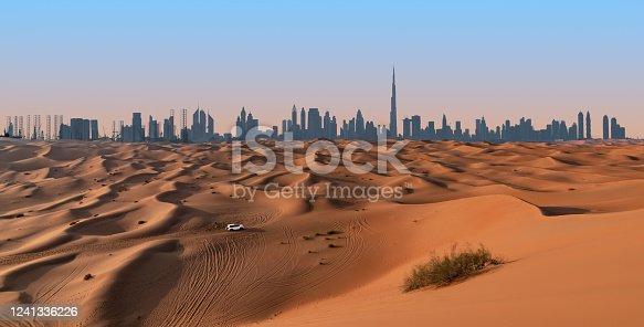 Dubai skyline on the horizon of a sand and dune landscape with tire tracks from a 4x4 vehicle during safari excursion. Blue sky at sunset.