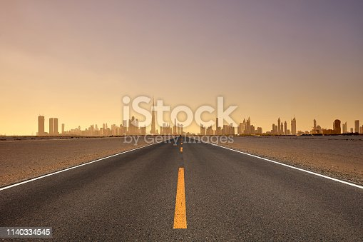Dubai skyline and highway at sunset, United Arab Emirates.