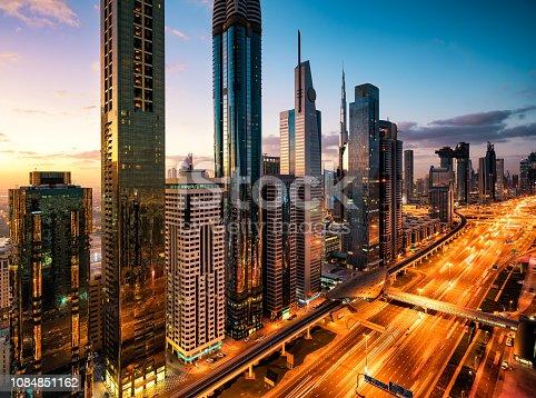 512697874 istock photo Dubai skyline at sunrise with illuminated road 1084851162