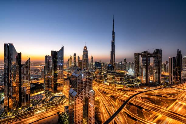 skyline von dubai bei sonnenaufgang mit verkehrsknotenpunkt und burj khalifa - sheikh zayed road stock-fotos und bilder