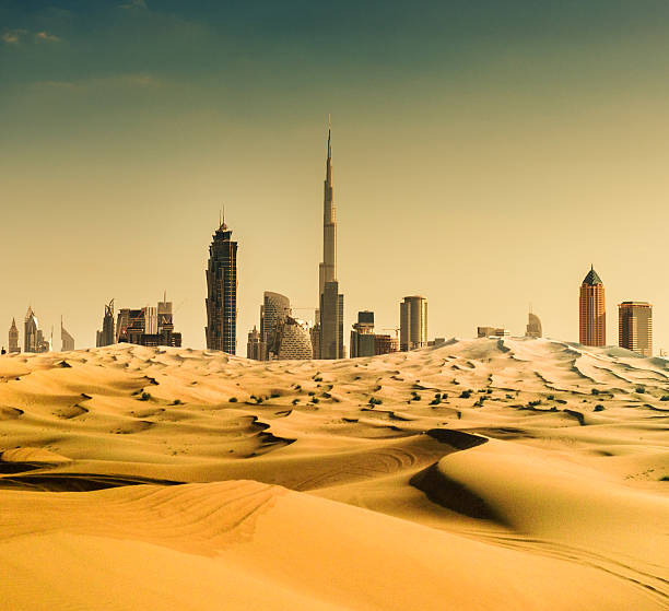 dubai skyline from the desert - sand dune stock photos and pictures