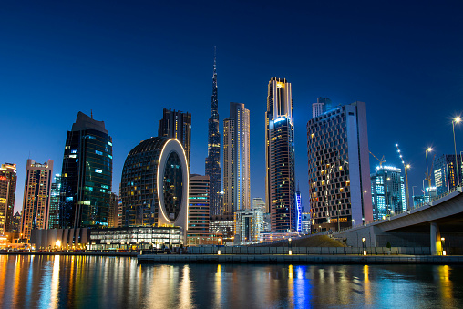 Dubai modern architecture landmark skyline view from the Marasi marina in city Business bay downtown area in the United Arab Emirates at blue hour at night