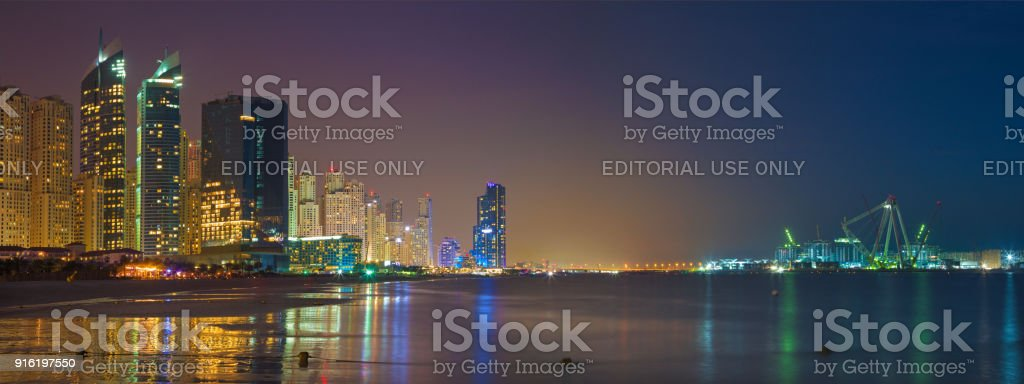 Dubai -  The nightly skyline panorama of Marina towers and worlds largest Ferris wheel under construction. stock photo