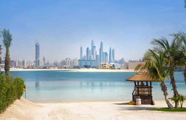dubai, vereinigte arabische emirate. palm jumeirah strand mit weißem sand. wolkenkratzer von dubai marina in der ferne - jumeirah stock-fotos und bilder