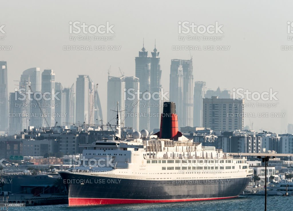 Dubai Uae Skyline With Queen Mary Ii In Foreground Stock