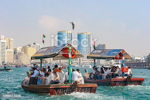 Dubai, United Arab Emirates - December 09, 2007: A couple of Abras or Water Taxis seen departing from Bur Dubai for Deira on the opposite side of the creek. On board are full loads of passengers including some tourists. It is a busy time of the day on Dubai Creek. In the background are the waterfront towers on the Deira side of the Creek. Photo shot, from a boat on the creek, in the afternoon sunlight; horizontal format. Copy space.