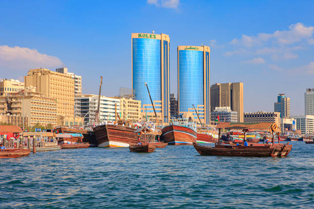 Dubai, United Arab Emirates - Abras Move To And From The Abra Station And Piers On The Deira Side Of Dubai Creek; In The Background Arab Dhows Moored At The Quayside On Deira. In The Far Background, Buildings And Towers O The Waterfront. Copy Space stock photo