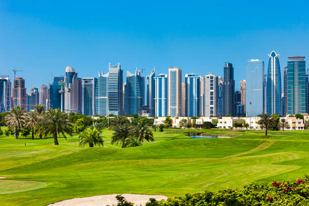 Dubai, United Arab Emirates - Golf Fairways In The Foreground And Modern Skyscrapers Against A Clear Blue Sky, In Jumeirah Lake Towers In The Background stock photo