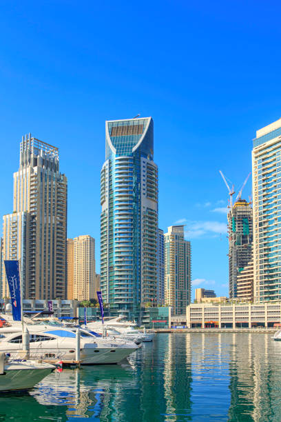 Dubai United Arab Emirates - Looking Across Boats Moored On Dubai Marina To Tall Waterfront Skyscrapers Against A Clear Blue Afternoon Sky. Reflections In The Water Enhance The Image. stock photo