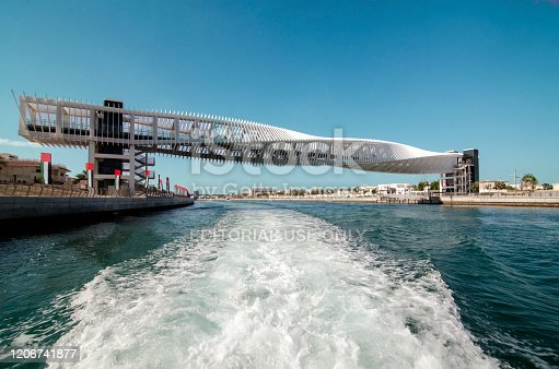 Dubai, United Arab Emirates - November 22, 2019: Riding a boat along the water canal in Dubai is not only a great way to see the city, and its futuristic buildings, but also see some of the Middle East traditional way of life. This foot bridge is almost a piece of art.