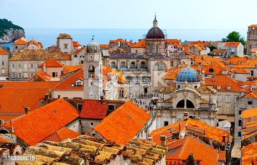Red tiled roofs of the historic walled city of Dubrovnik with Lokrum Island in the distance.