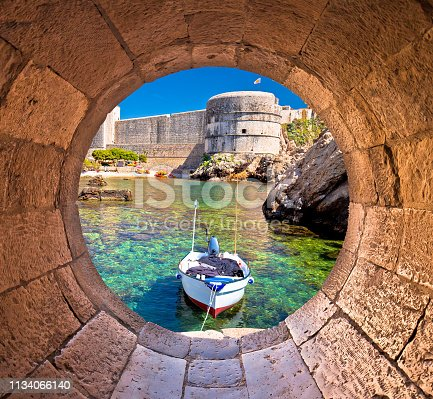 istock Dubrovnik small harbor under city walls view through stone carved window 1134066140