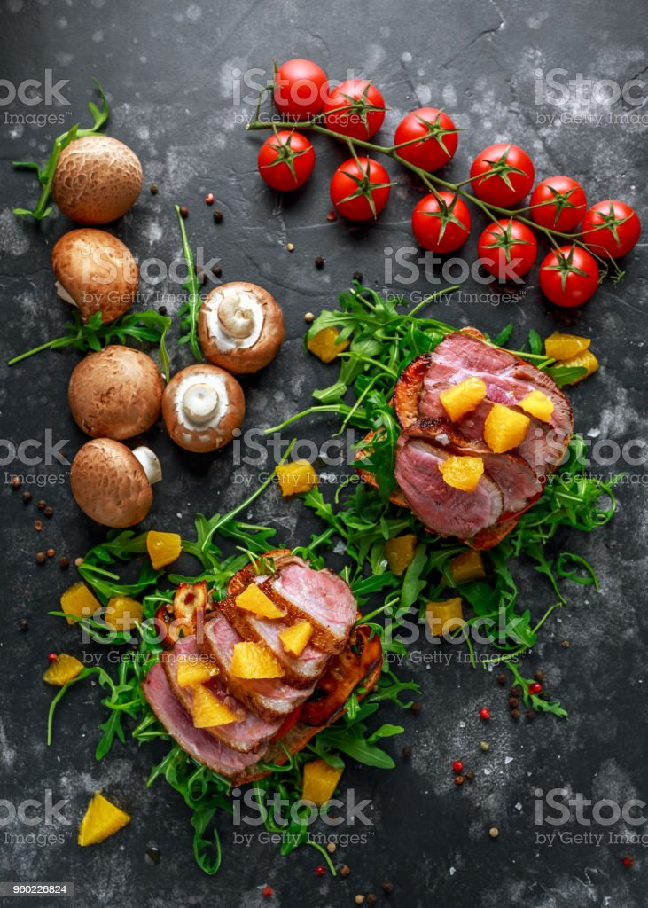 Duck breast steak slices on wild rocket pillow sandwich with orange bits, mushrooms and balsamic vinegar drizzle stock photo
