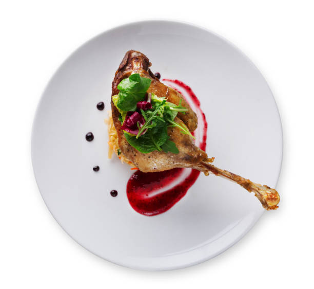 Duck confit with berry sauce isolated on white stock photo