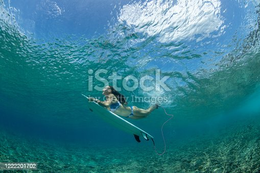Surfer girl duck dives a beautiful clear wave