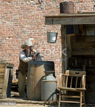 A gunman takes shelter behind a barrel.
