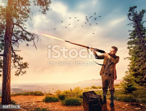 658114236 istock photo Duck hunter in hunting clothing aims an old rifle 658114476