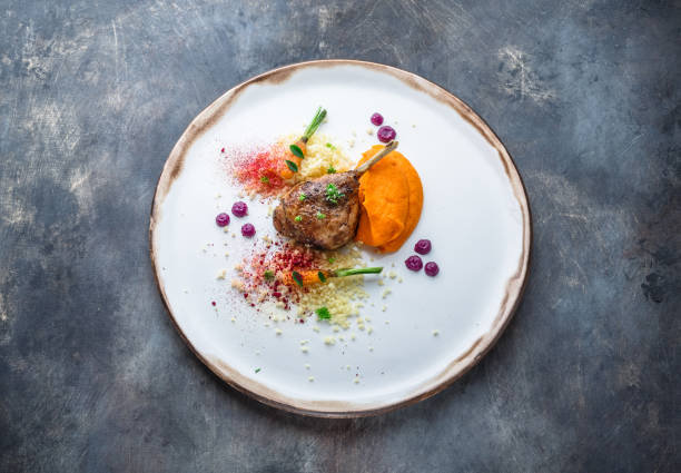 Duck leg confit with batat puree, carrots and couscous, restaurant meal stock photo