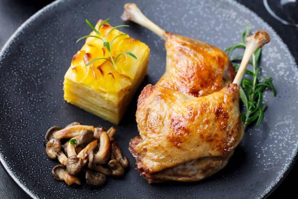 ente beine-confit mit kartoffel-gratin und pilzsauce. restaurant mit. - gänsefett stock-fotos und bilder
