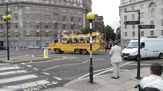 London, United Kingdom - July 31, 2009: Duckboat tour bus filled with tourists in Southbank London. The duck boat converts from a tour bus to a boat and offers tourists tours that cover landmarks both on land and from the River Thames. There are other people walking on the sidewalk and in the background.