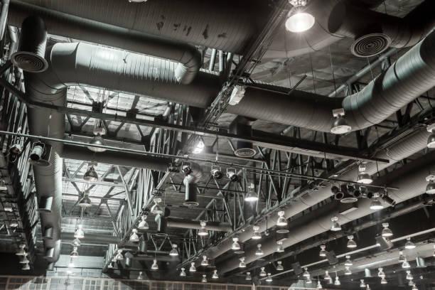 hvac duct reiniging, ventilatie pijpen in zilveren isolatiemateriaal opknoping van het plafond in het nieuwe gebouw. - elektrische fitting stockfoto's en -beelden