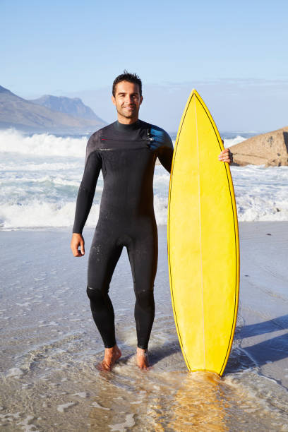 Dude with board Surfer dude in wetsuit standing with board on beach wetsuit stock pictures, royalty-free photos & images