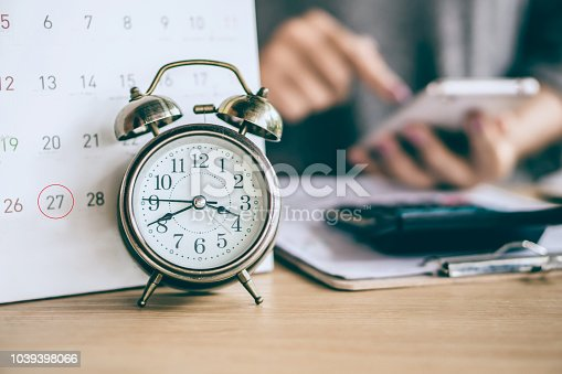istock due date calendar and alarm clock with blur business woman hand calculating 1039398066