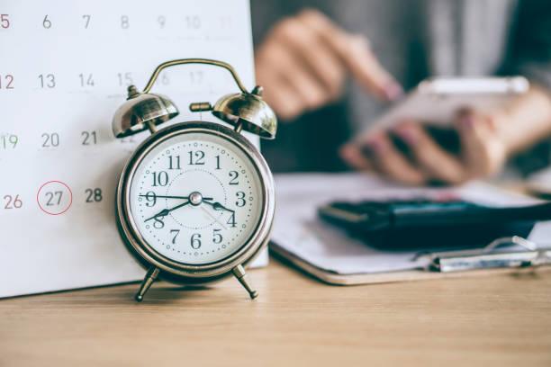 kalendarz terminowy i budzik z rozmyciem strony kobiety biznesowej obliczania - czas zdjęcia i obrazy z banku zdjęć