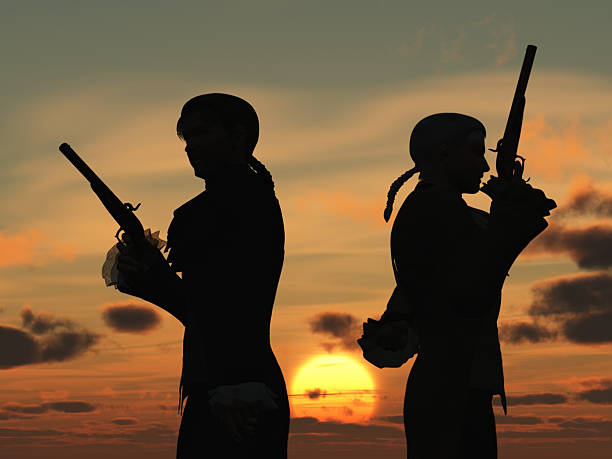 Duellists silhouetted against the rising sun stock photo
