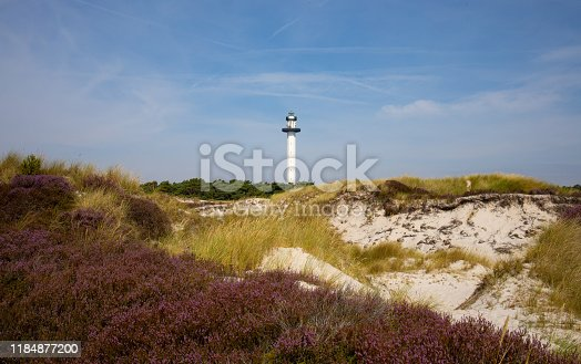 high lighthouse on a sandy shore full of dunes