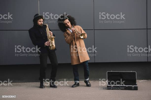 duet of street jazzmen playing trumpet and saxophone outdoors